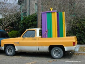 Pickup truck carrying purple, green and gold porta potty
